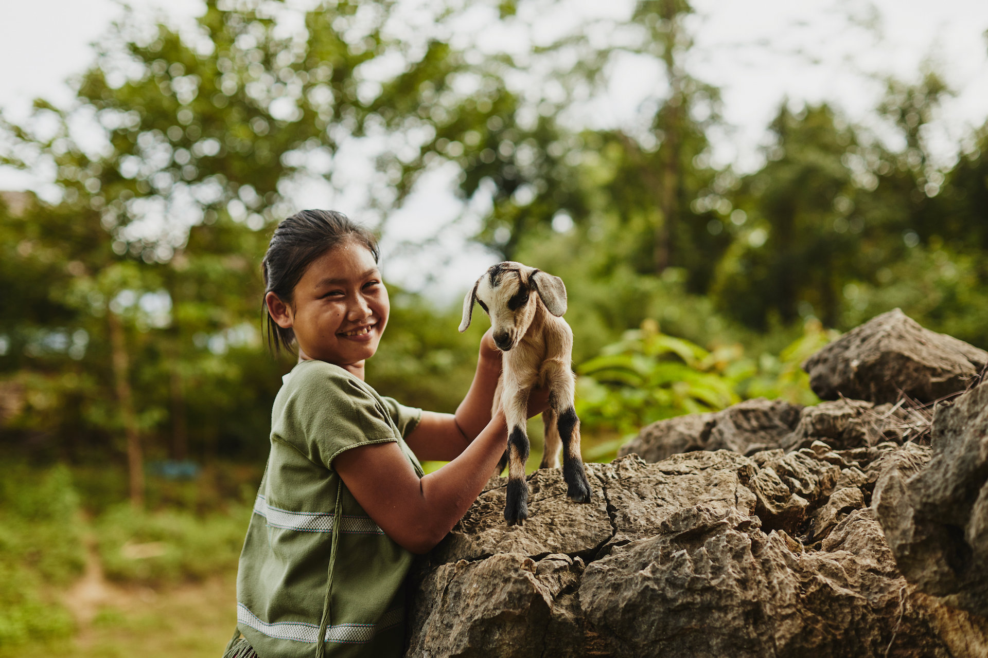 A young Thai girl in a green top holds a baby goat on top of a large boulder.