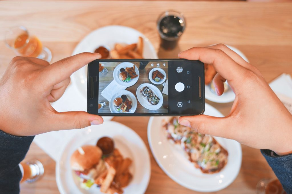 Two hands holding an iPhone over a table of food, taking a picture of it.