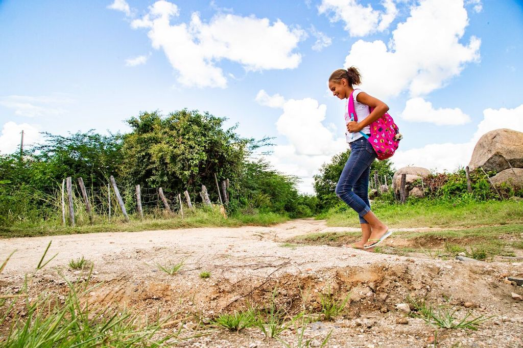 A girl in jeans and a t-shirt, carrying a pink backpack, walks in a field.