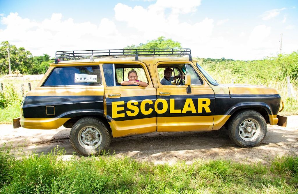 """A girl sits in a yellow and black car that has """"Escolar"""" printed on the side."""