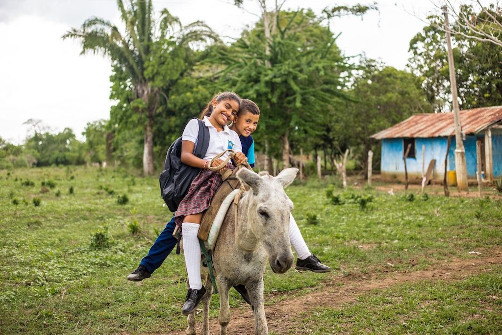 Two children, a sister and brother, sit on a donkey.