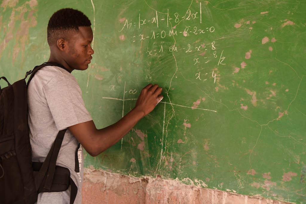 Abdoul writes on a green chalk board.