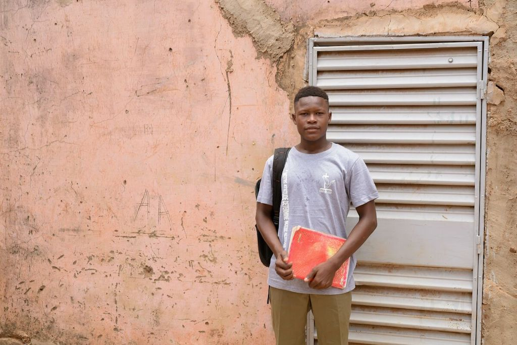 Abdoul stands boy a door, wearing a backpack and holding a red notebook.