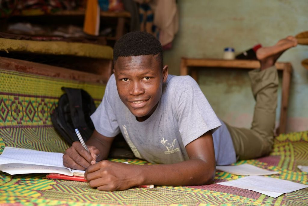 Abdoul lays on the floor of his home, working on homework.