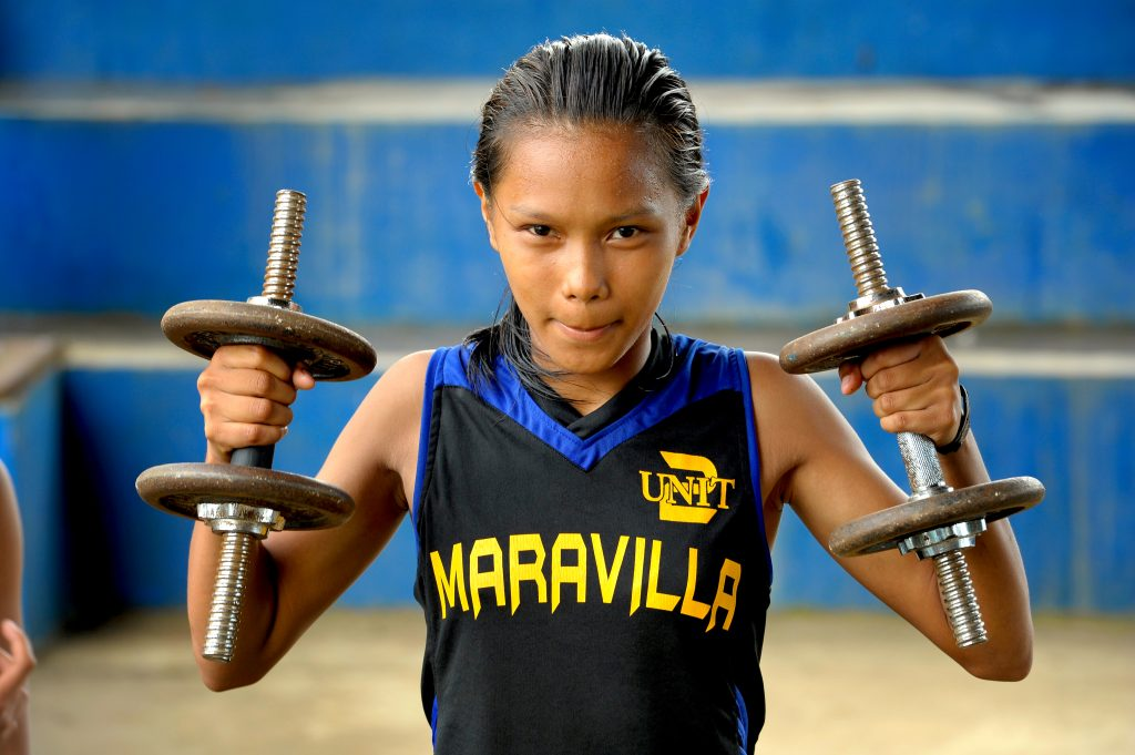 Kenia wears a black and blue jersey and lifts two weights making a tough face