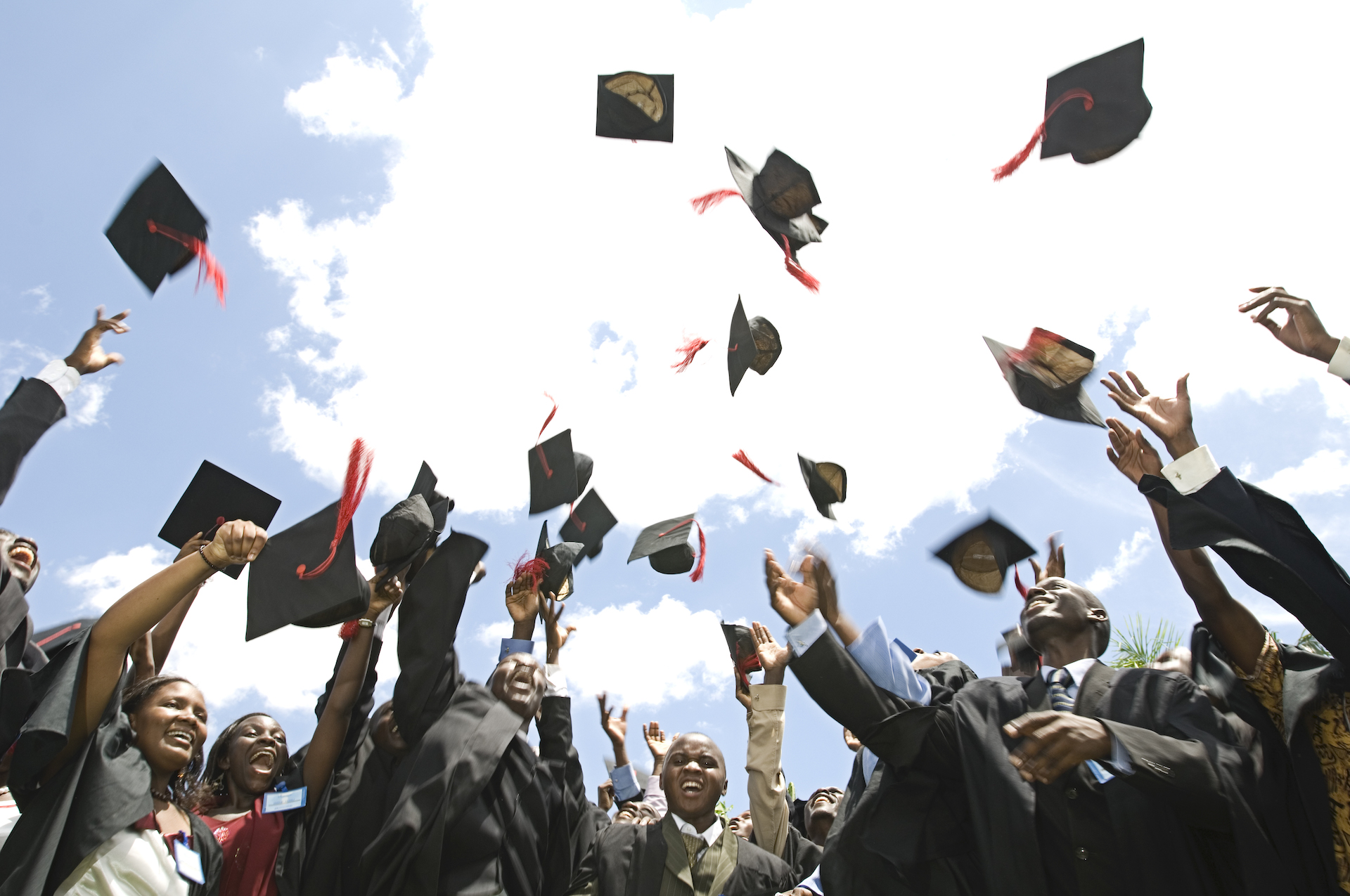 A group of students throw their graduation hats in the air.