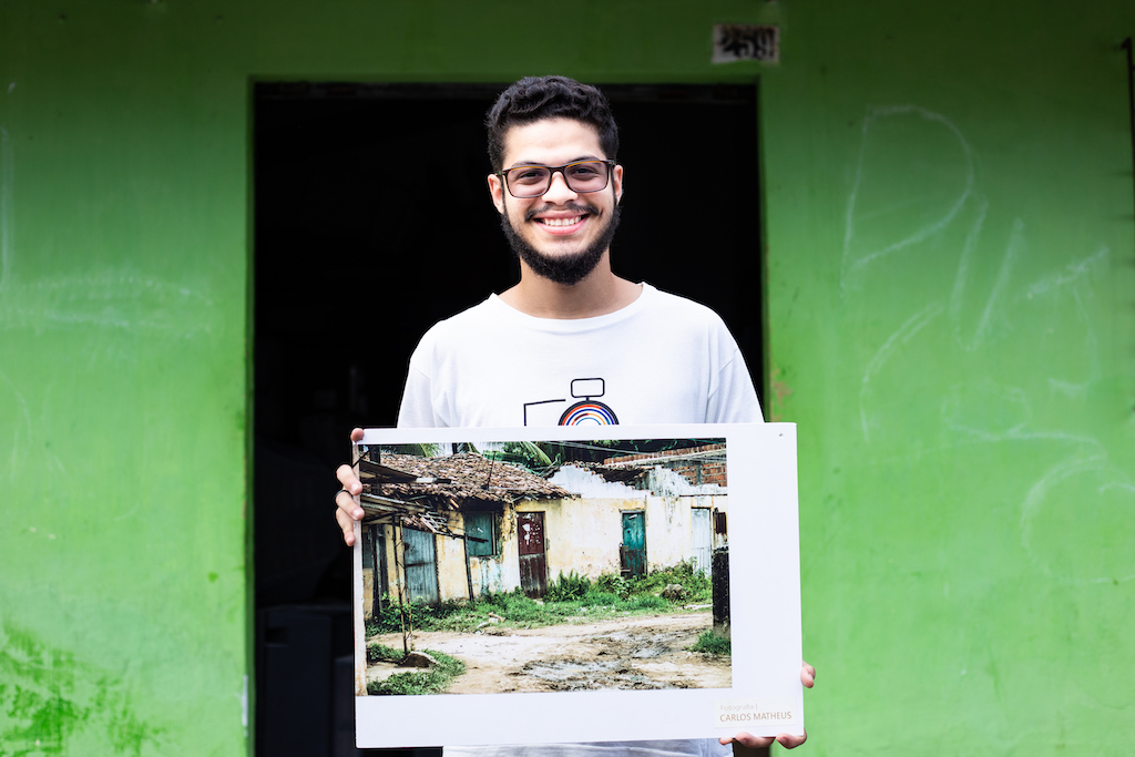 Matheus stands in front of a green building, holding a photograph he took of a home.