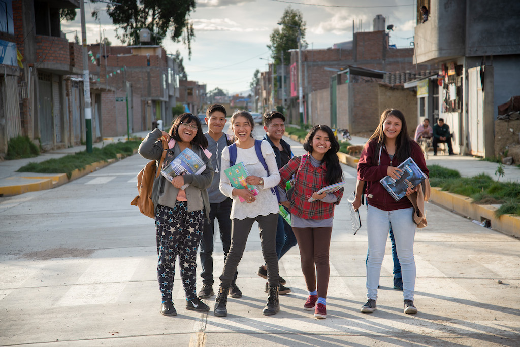 A group of students smiling in the street.