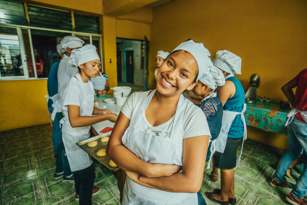 A young woman in an apron and chef's hat smiles at the camera as other bakery students work behind her.