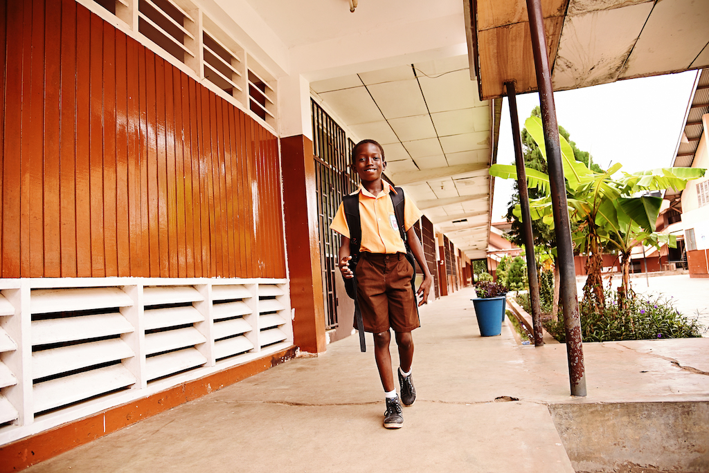 A boy walks on a path outside his school, wearing a uniform and backpack.