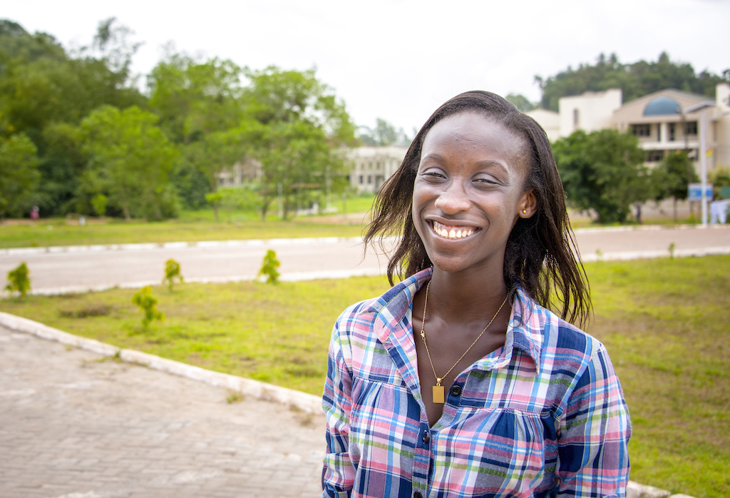 A portrait of Georgina, smiling on her university campus.
