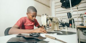A boy using sewing machine to make bags.