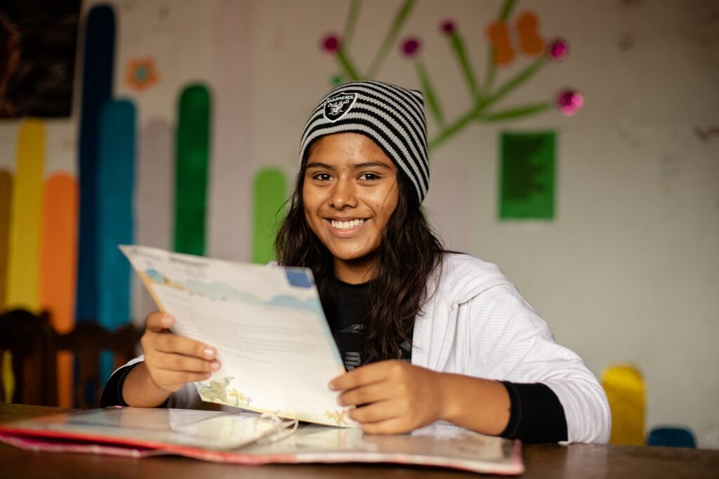 Girl smiles and looks at the camera as she reads a letter from her sponsor. She's wearing a toque.