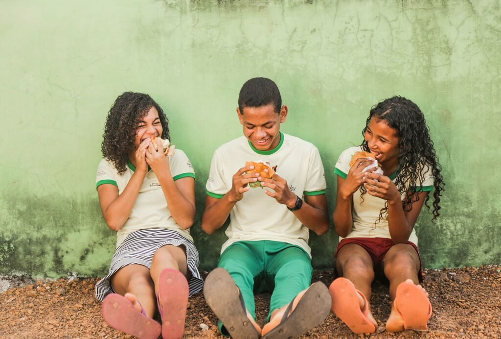 Three teens smile while eating a hamburger each. They are lsitting against a green wall.