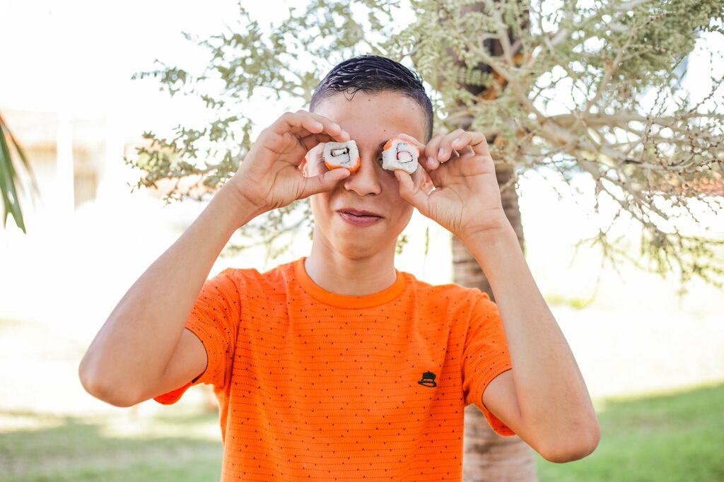 A teen boy wearing an orange t-shirt hold sushi rolls to his eyes like glasses.