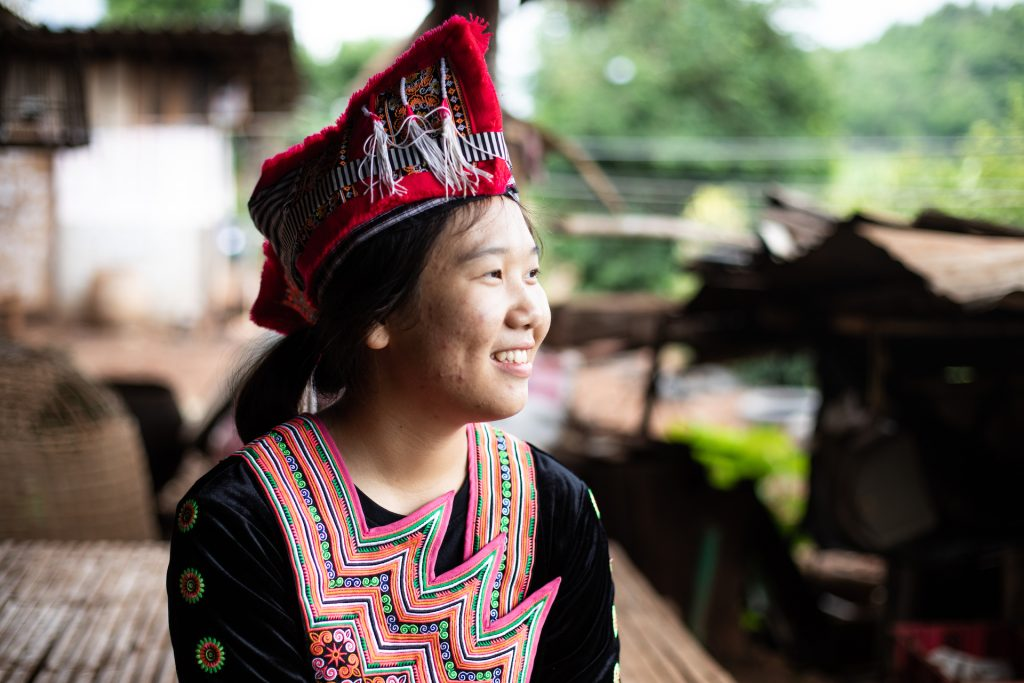 Girl wearing a traditional hat smiles looking off into the distance.