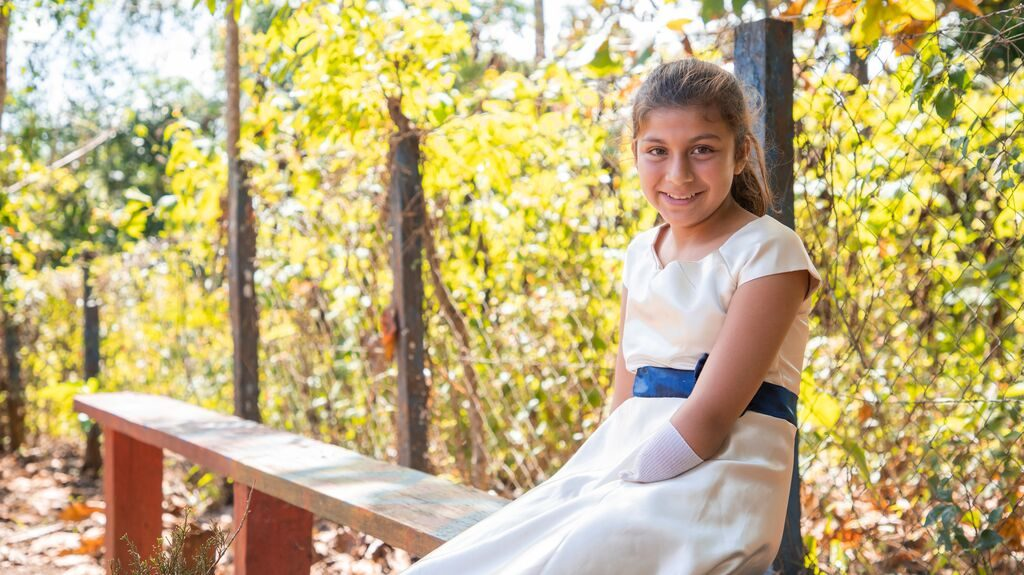 Girl wearing a white dress sits on a bench infront of trees. She wear a sock on her hand. She is beautiful.