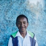 A portrait of an Ethiopian teen, against a blue wall wearing a white shirt and blue vest.