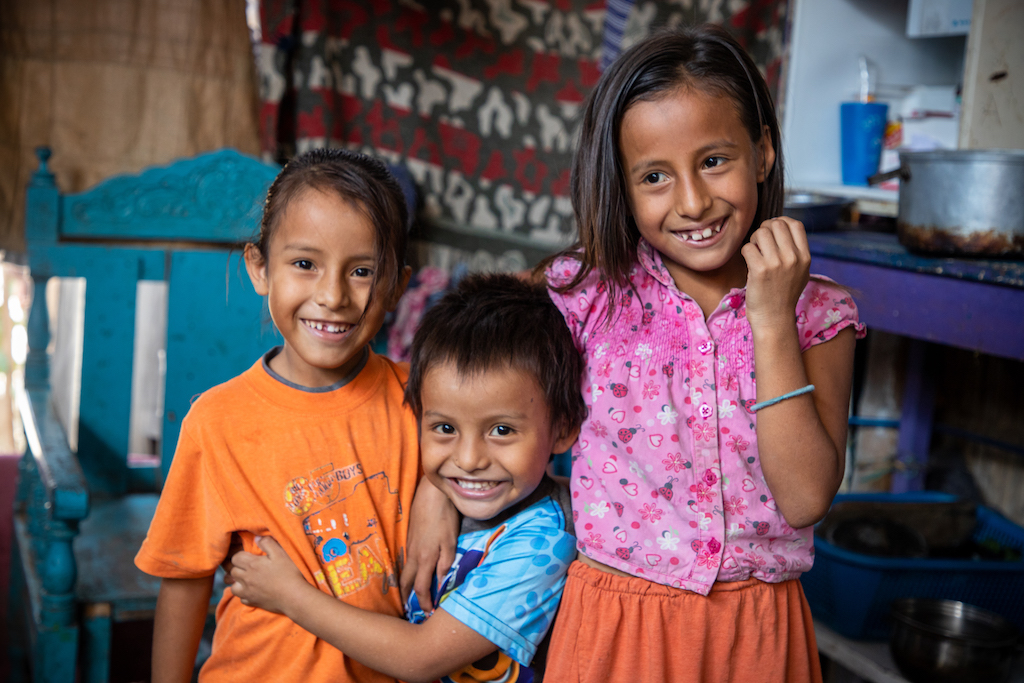 Three Ecuadorian children laughing and hugging each other.