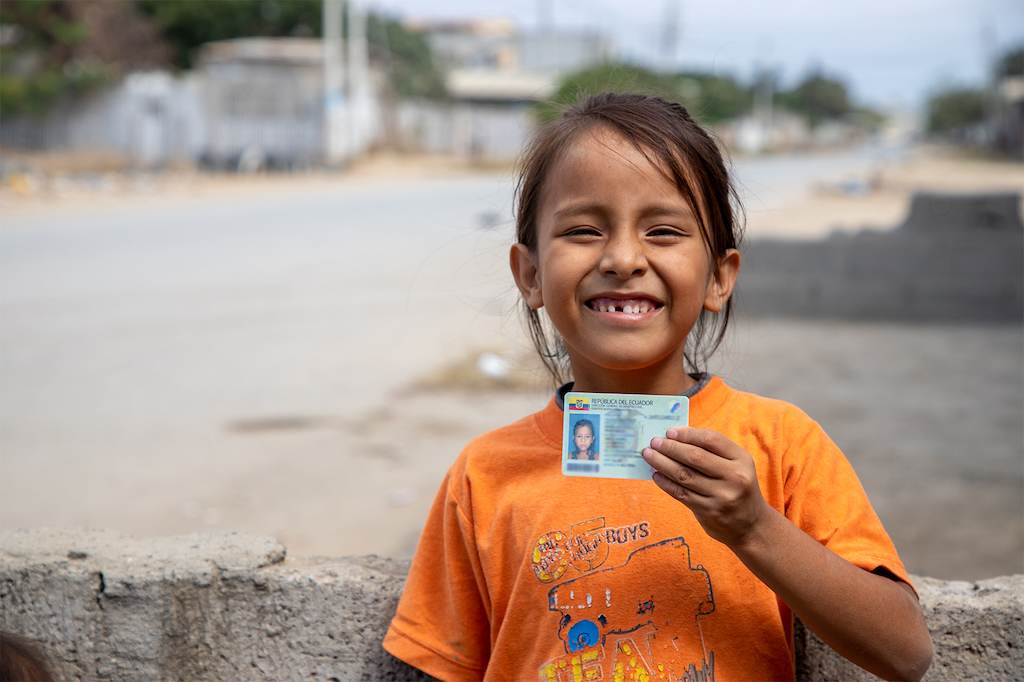 Maria Belen smiles and holds up her identity card.