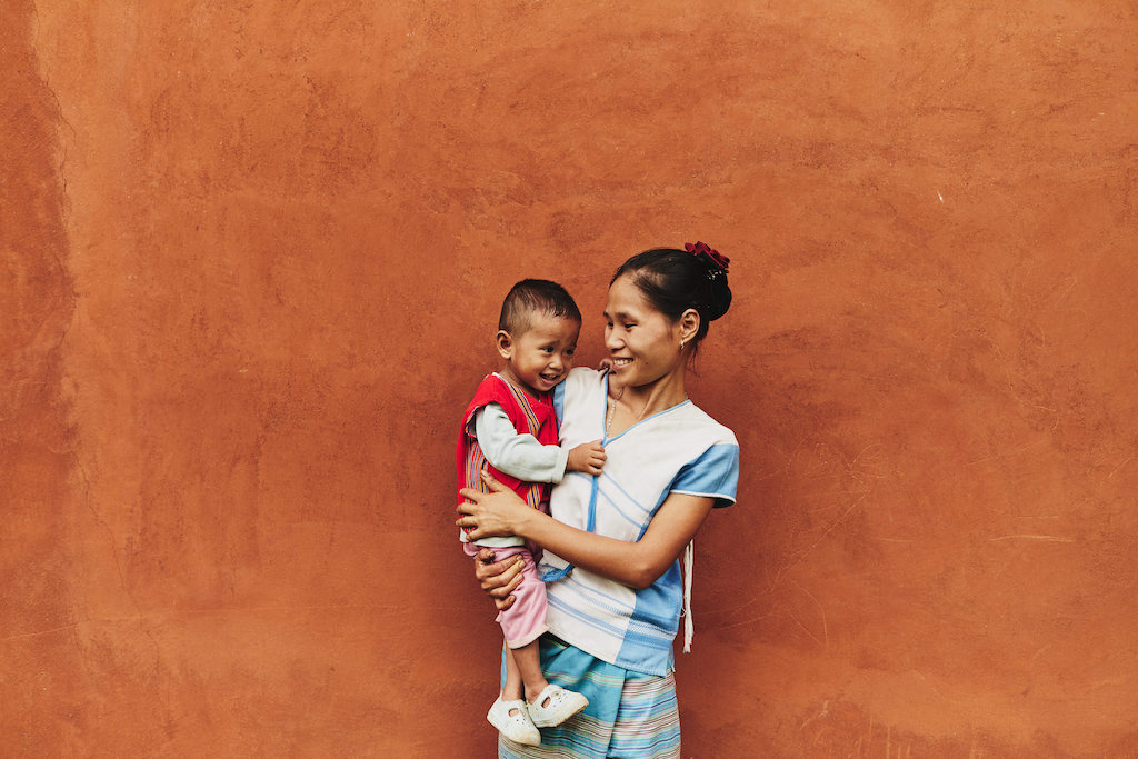 A mother holds a toddler. They are both smiling. They are standing against a rust orange wall.