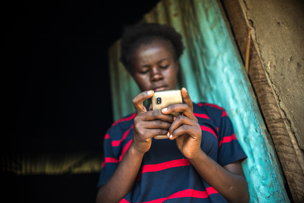 A young Kenyan girl looks down at a mobile phone.