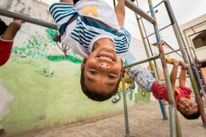 A boy hangs upside down from a playground structure.