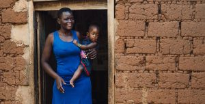 A woman stands in the door of mud brick. She holds a baby on her hip and smiles.