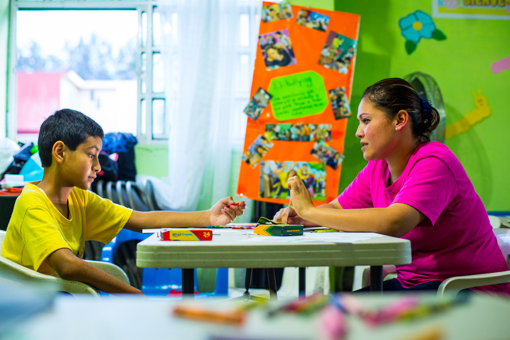 Hector sits across a table from Lupita at the Compassion centre.
