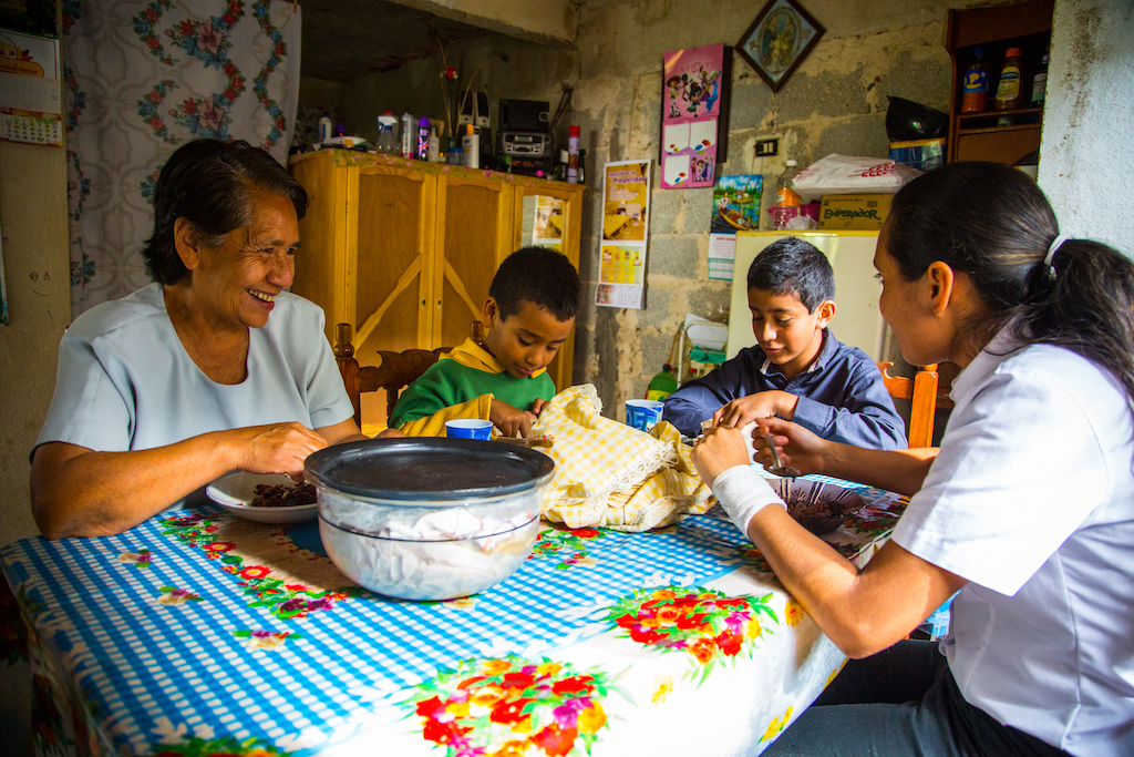 Hector, his brother, aunt and grandmother sit around table in their home eating a meal together.