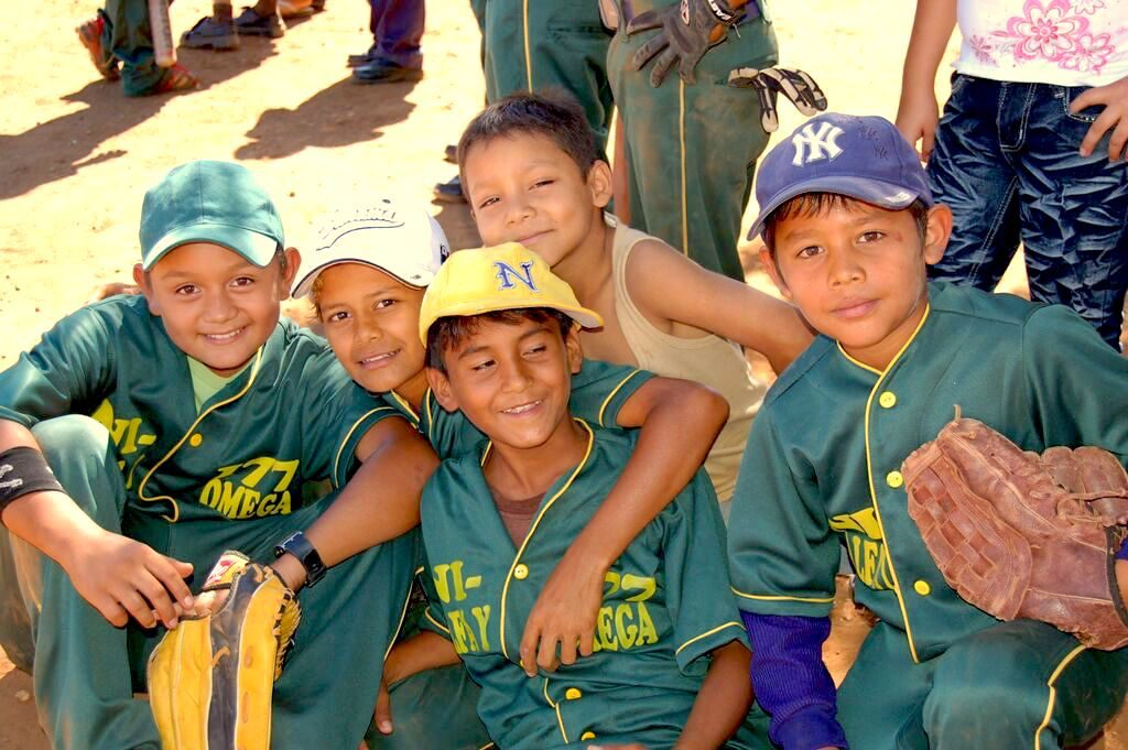 A group of boys wearing green jerseys smiling at the camera