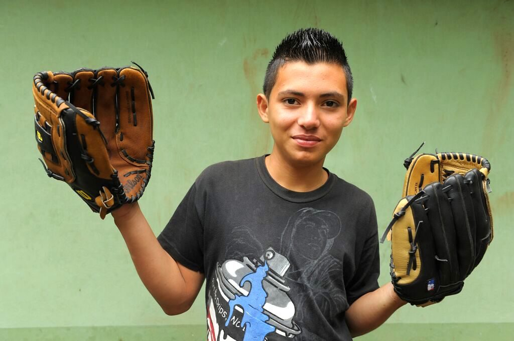 Carlitos holds two baseball gloves in his hands