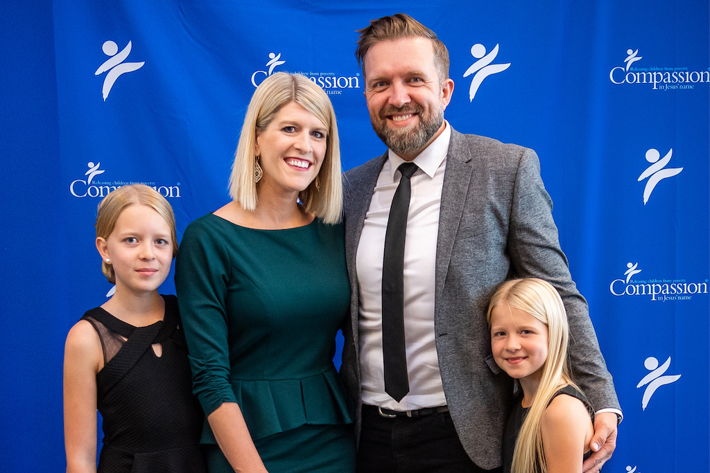 A portrait of the Alley family in front of a blue Compassion backdrop.