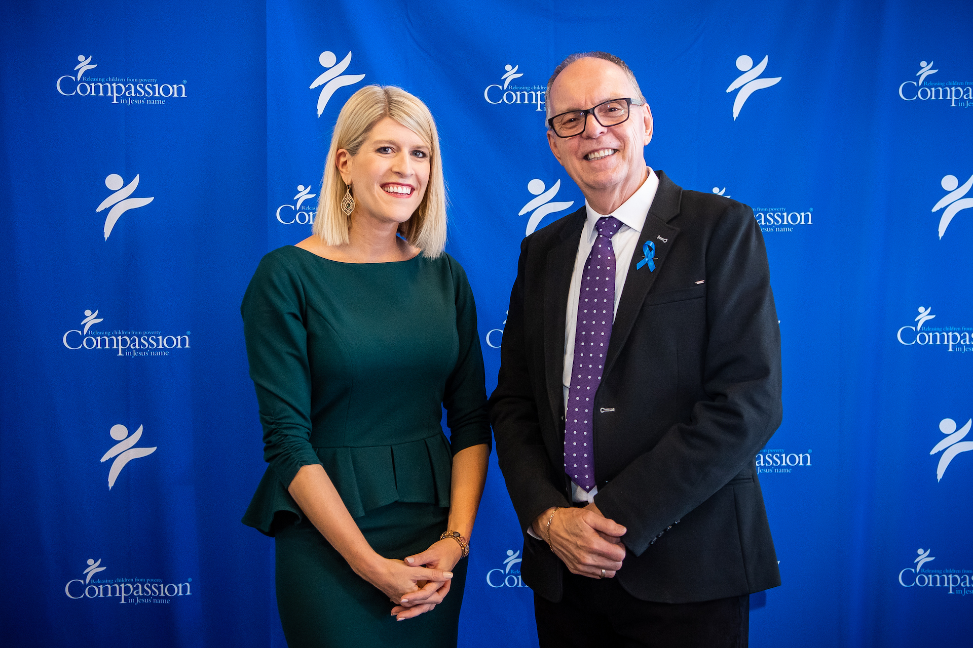 Allison and Barry pose in front of a blue Compassion backdrop.