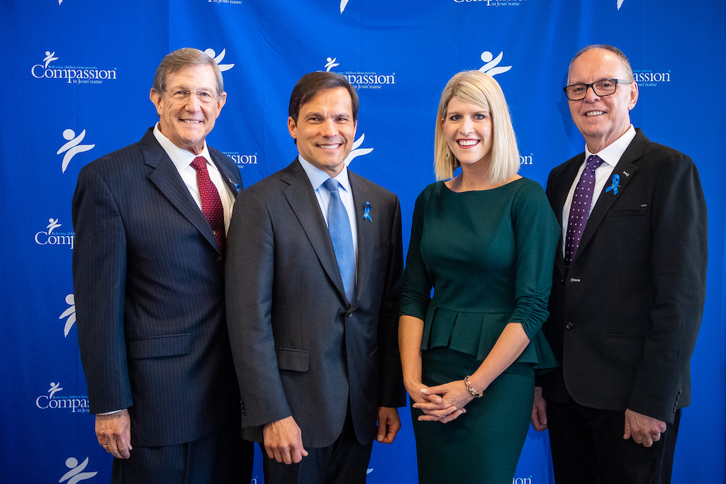 "Dr. Wess Stafford, Santiago ""Jimmy"" Mellado, Allison Alley and Barry Slauenwhite pose in front of a blue Compassion backdrop."