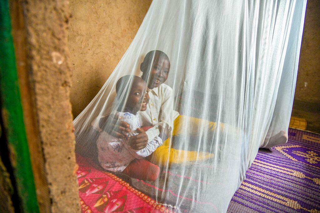 Two little boys sit on a bed under a mosquito net. They're smiling.