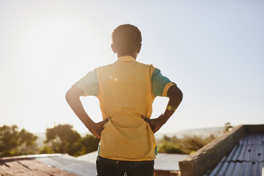 Little boy with his back to the camera wearing a yellow shirt