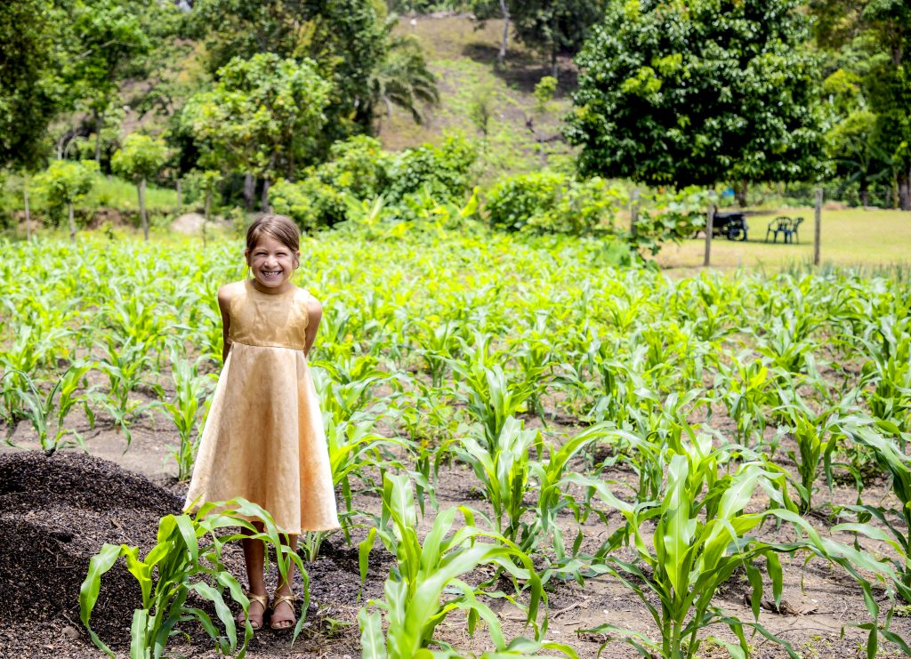 girl wearing a golden fress stands in a field smiling