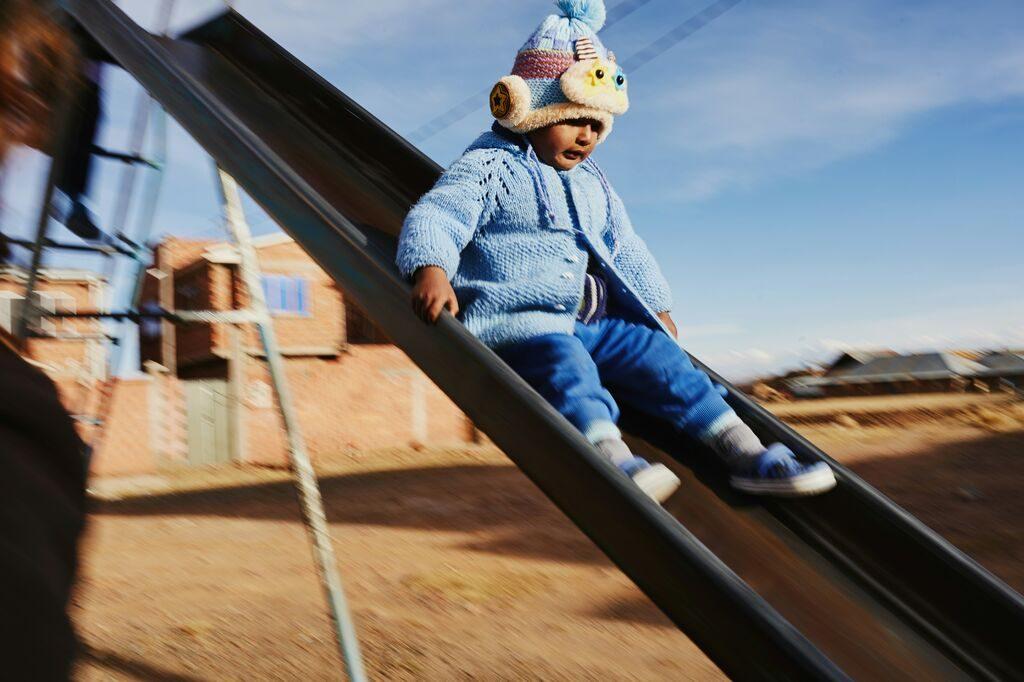 Little girl slides down the slide in knitted hat