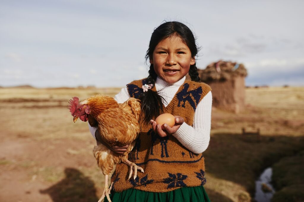 Girl holds a chicken in one hand and an egg in another