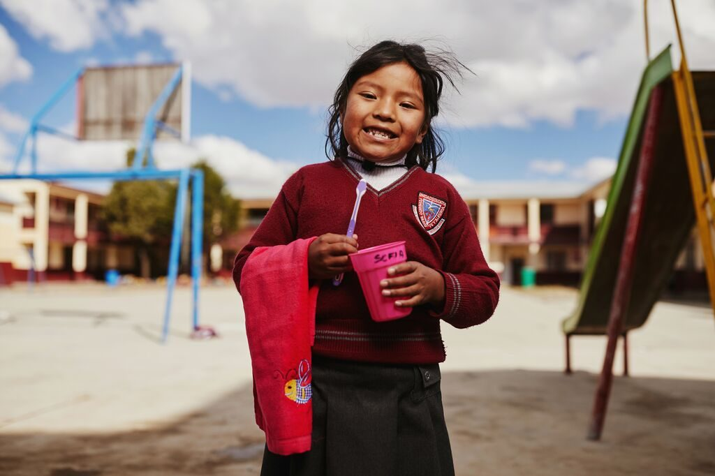 gIRL HOLDS A TOOTHBRUSH AND A CUP
