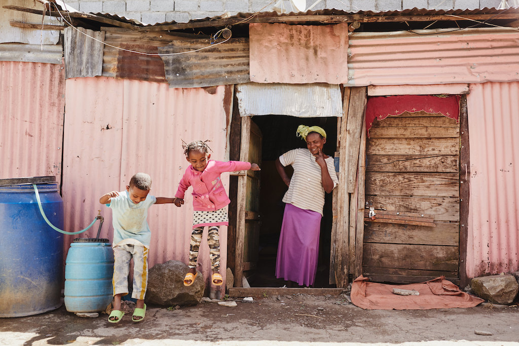 A mother stands in the door of her home, watching her two young children jump.