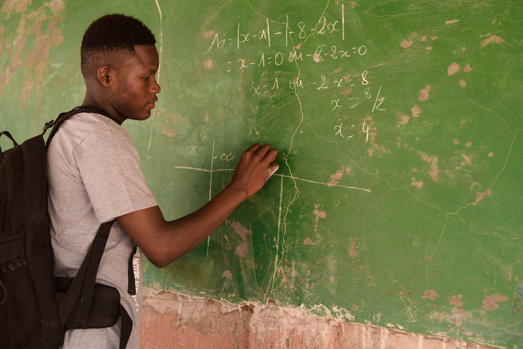 A young man writes on a green chalkboard.