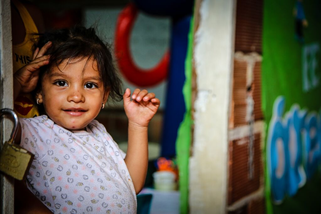 Little girl smiles at the doorway of her home