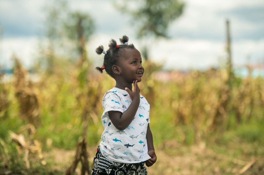 Little girl smiles off into the distance in a field
