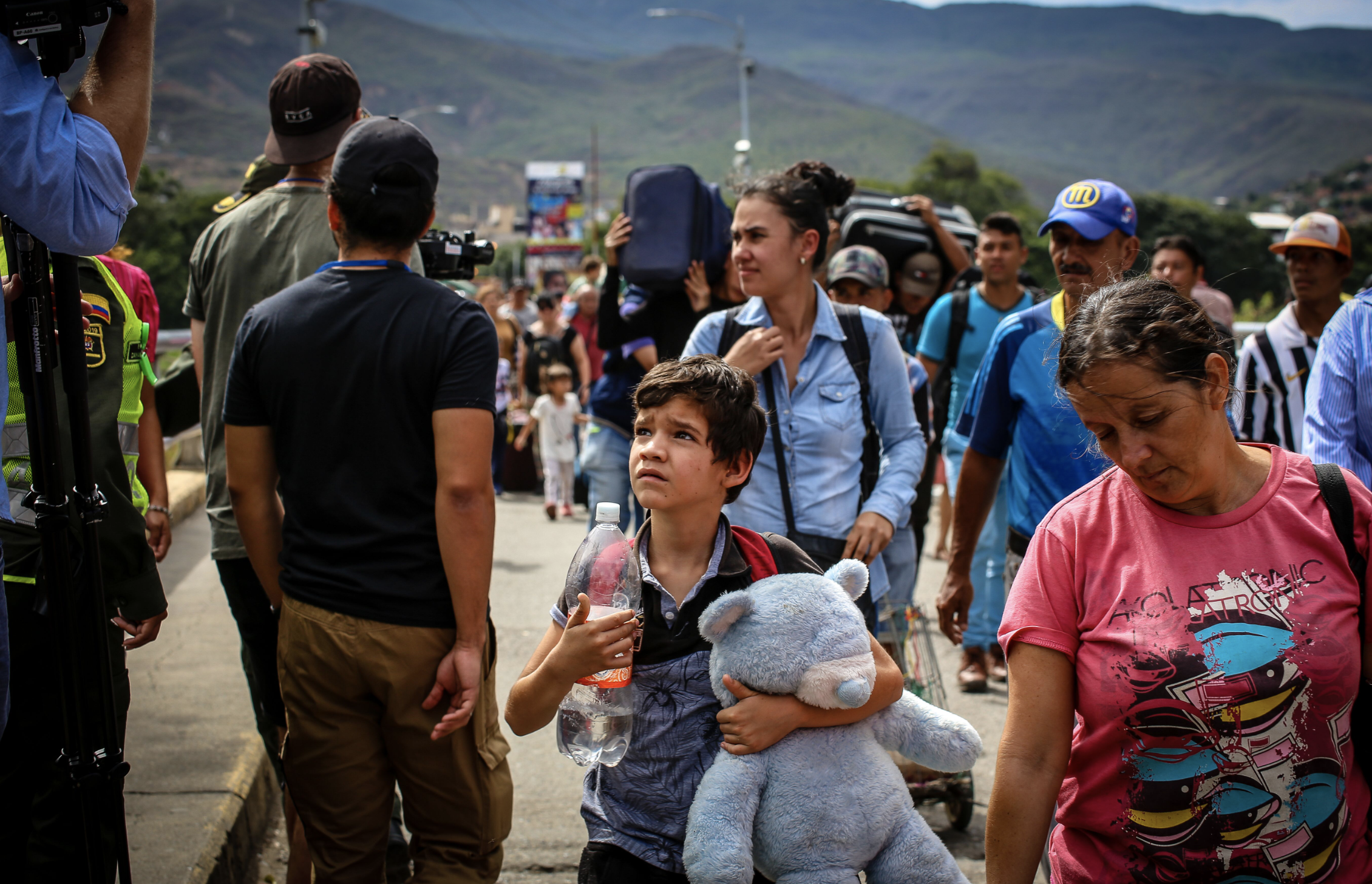 A young boy, teddy bear in hand, walks toward the Colombian border