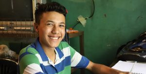 A teenage boy sits at a table in a green classroom and smiles.