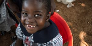 A Ugandan child sits in a red plastic chair and smiles at the camera.