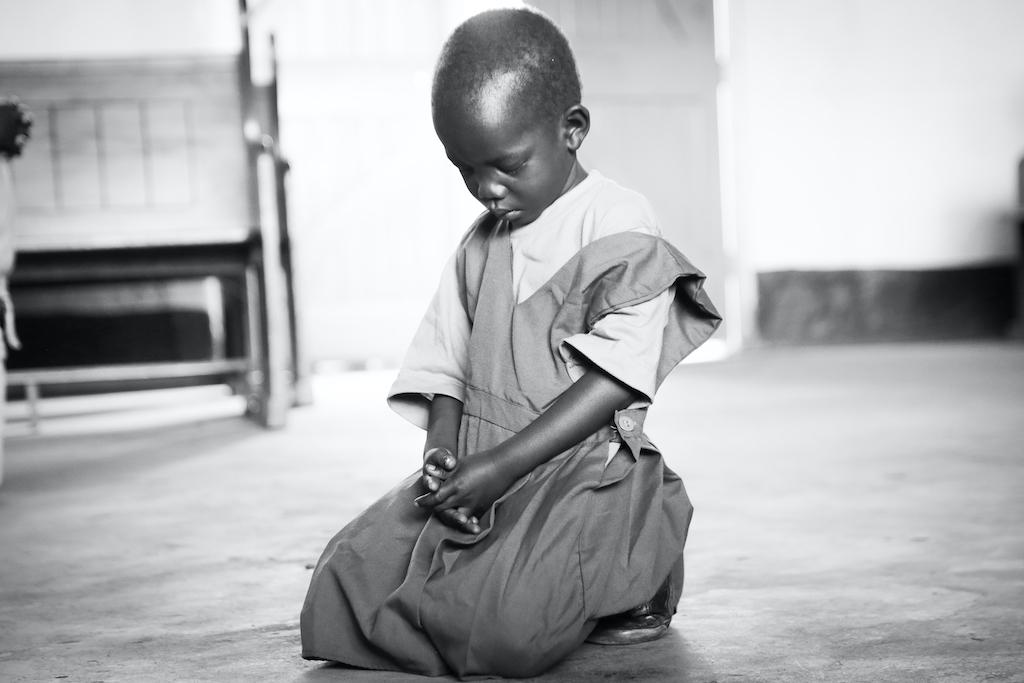 A child kneeling in prayer.