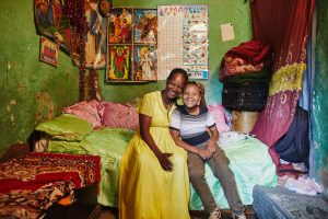 A mother and daughter sit on the bed and smile at the camera in their one-room home.